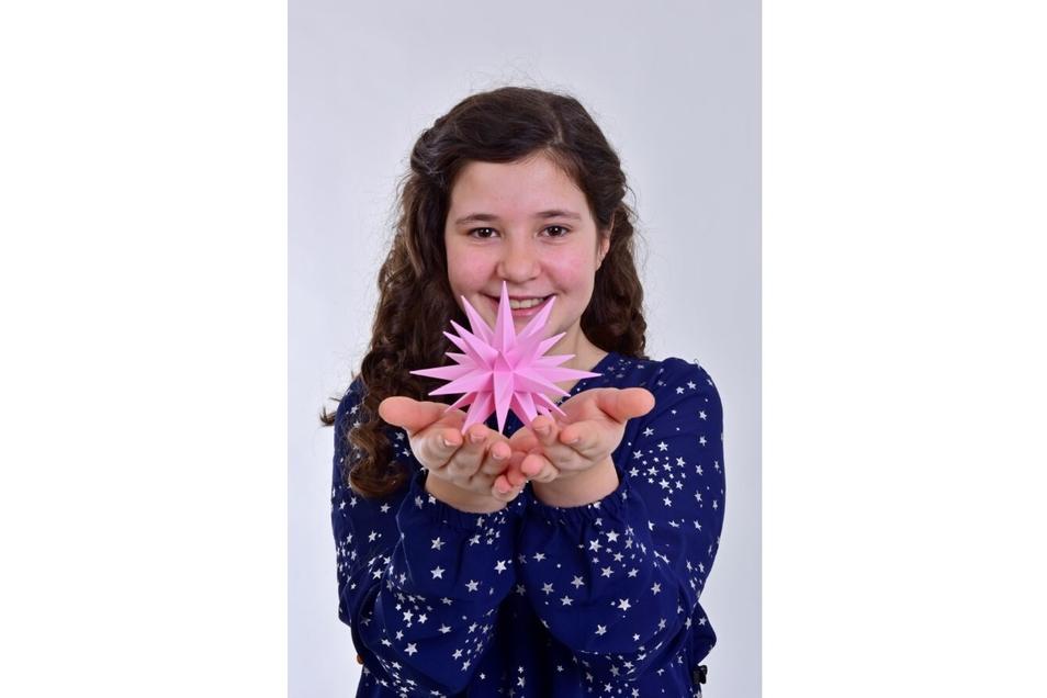 Sternekind Lucy präsentiert den neuen rosafarbenen Kunststoffstern mit 13 Zentimeter Durchmesser.