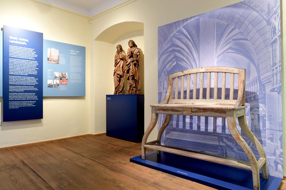 Die alte Orgelbank und die Altarfiguren Johannes der Täufer und Johannes der Evangelist flankieren das Thema Glauben und Religion.