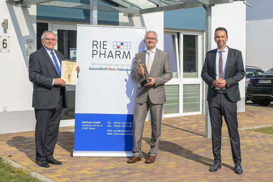 Helfried Schmidt (v.l.n.r.) von der Oskar-Patzelt-Stiftung überreichte jetzt den Mittelstandspreis an Apotheker Marko Eschmann von der Riepharm GmbH, Riesas OB Marco Müller (CDU) freut sich.