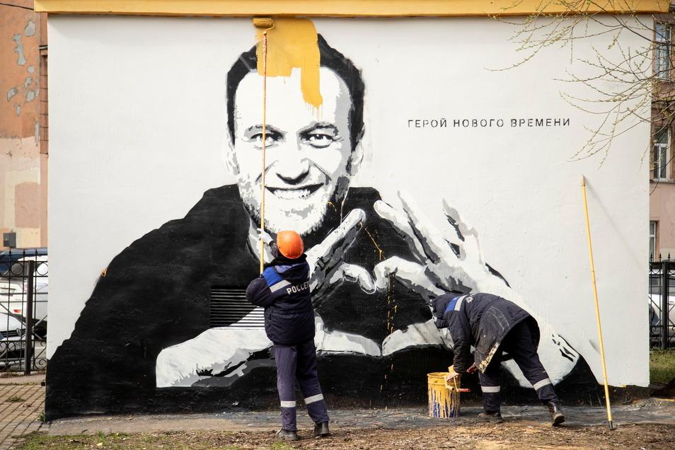 In St. Petersburg übermalen städtische Arbeiter ein Graffiti mit dem Konterfei des inhaftierten russischen Oppositionsführers Nawalny.