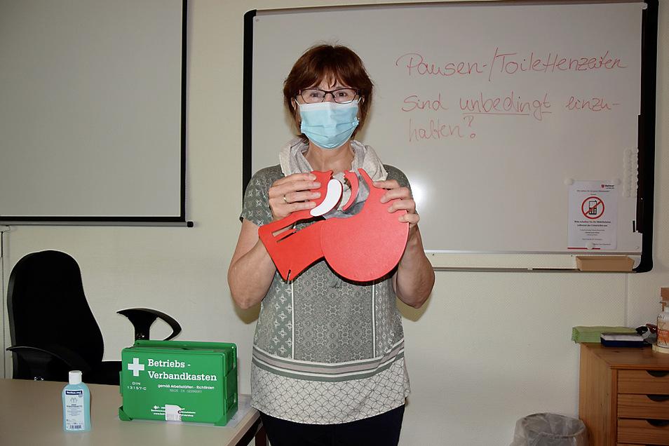 Erste-Hilfe-Ausbilderin Irina Mücke im Unterrichtsraum mit einem Modell der oberen Atemwege des menschlichen Körpers.