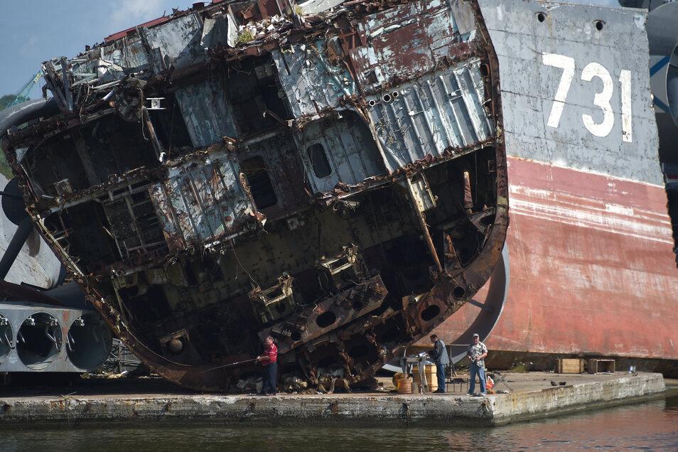 Männer angeln in Kaliningrad vor einem Schiffswrack der russischen Marine.