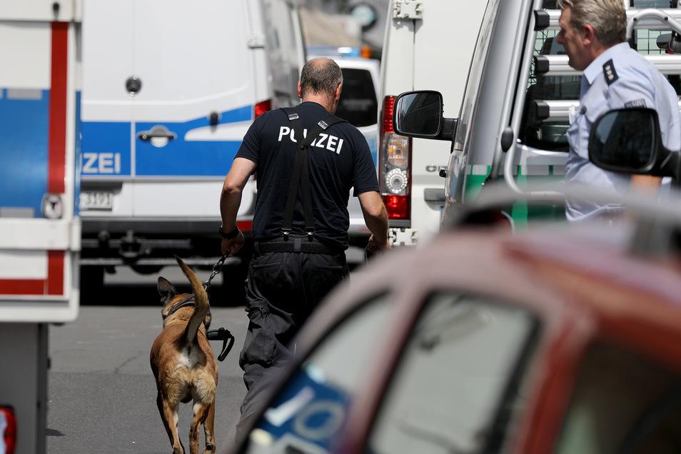 Ein Polizist geht bei der Razzia mit einem Sprengstoffspürhund zu einem Wohnhaus in Köln.
