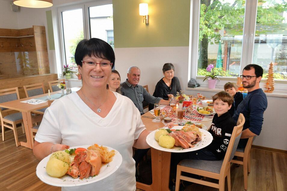 Janine Schöbel-Kunath kommt mit dampfenden Tellern aus der Küche zu Familie Patzig aus Tharandt, die bei einem Ausflug zu den ersten Gästen der neuen Waldschänke gehörten.