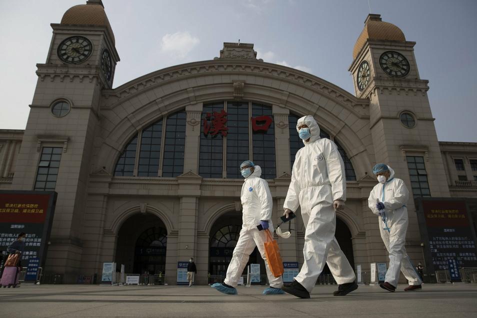 China, Wuhan: Arbeiter in Schutzanzügen laufen am Bahnhof Hankou vorbei. Ein Expertenteam will in China im Auftrag der Weltgesundheitsorganisation nach den Ursprüngen des Coronavirus suchen.