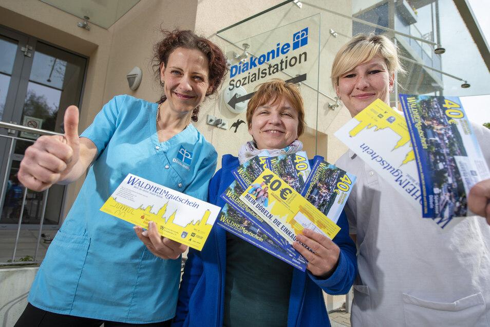 Die Leiterin der Sozialstation der Diakonie in Döbeln, Kerstin Georgi (Mitte), verteilt Döbeln- und Waldheim-Gutscheine an ihre Mitarbeiter. Darüber freuen sich Betreuerin Gesine Hoehne (links) und Altenpflegerin Julia Lopez.
