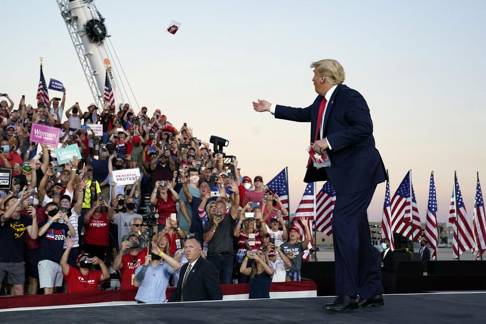 Donald Trump wirft Gesichtsmasken in die Menge, als er zu einer Wahlkampfkundgebung am Orlando Sanford International Airport eintrifft.