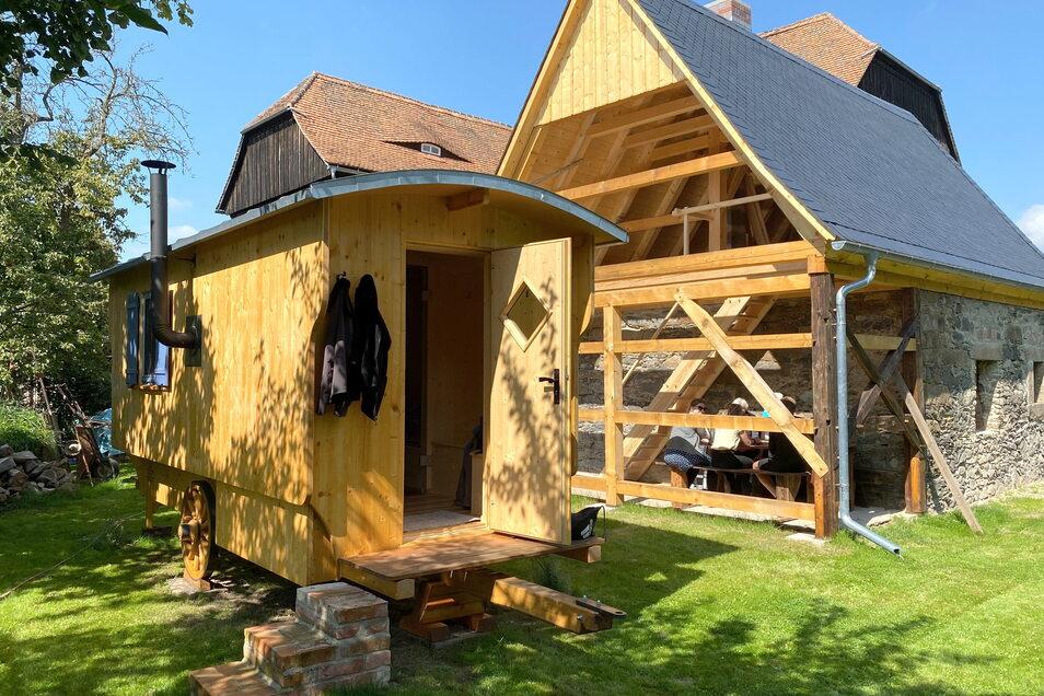 Im Garten steht ein uriger Saunawagen, der auch gemietet werden kann. Das ehemalige Stallgebäude ist bereits saniert. Hier soll künftig in Holzöfen gebacken und gekocht werden.