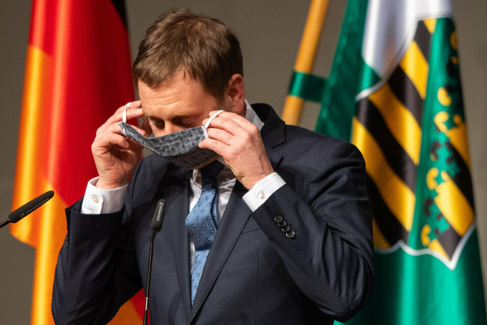 Michael Kretschmer (CDU) zieht nach seiner Rede seinen Mundschutz an.