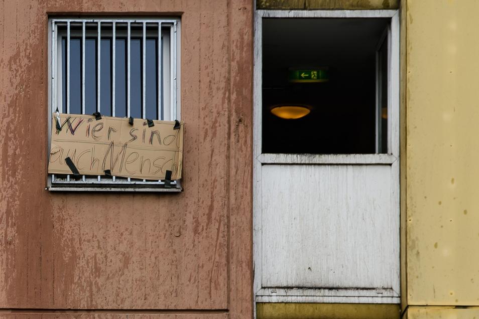 """Am Fenster eines unter Quarantäne gestellten Wohnhauses in Göttingen hängt eine Plakat mit der Aufschrift """"Wier sind auch Mensch""""."""