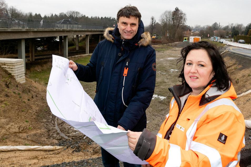 Isabel Pfeiffer, Pressesprecherin des Landesamtes für Straßenbau und Verkehr (Lasuv), und Andreas Biesold, Leiter der Bautzener Lasuv-Niederlassung, stehen mit den Plänen an der Baustelle in Großharthau. Die neue Brücke über die Bahngleise wird rechts neb