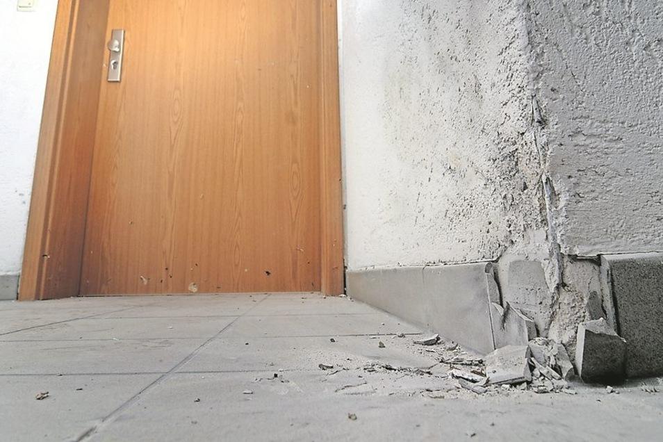 Im Hausflur im zweiten Stock ist der Sprengsatz neben einer Wohnungstür explodiert. Fliesen und Putz wurden zertrümmert. Splitter stecken im Rahmen und dem Blatt der Wohnungstür, die aus den Angeln gerissen wurde. Die gröbsten Schäden wurden repariert, da