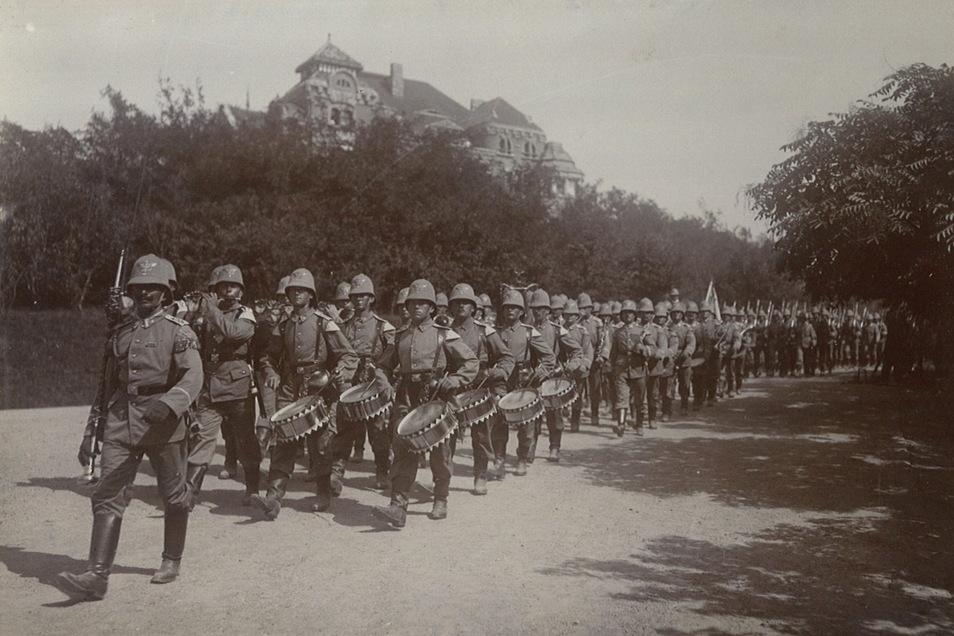 """Die """"Musterkolonie"""" Kiautschou steht unter Kontrolle des Militärs. Hier paradiert Karl Kockischs III. Seebataillon in der Hauptstadt Tsingtau unterhalb des Gouverneurshauses."""