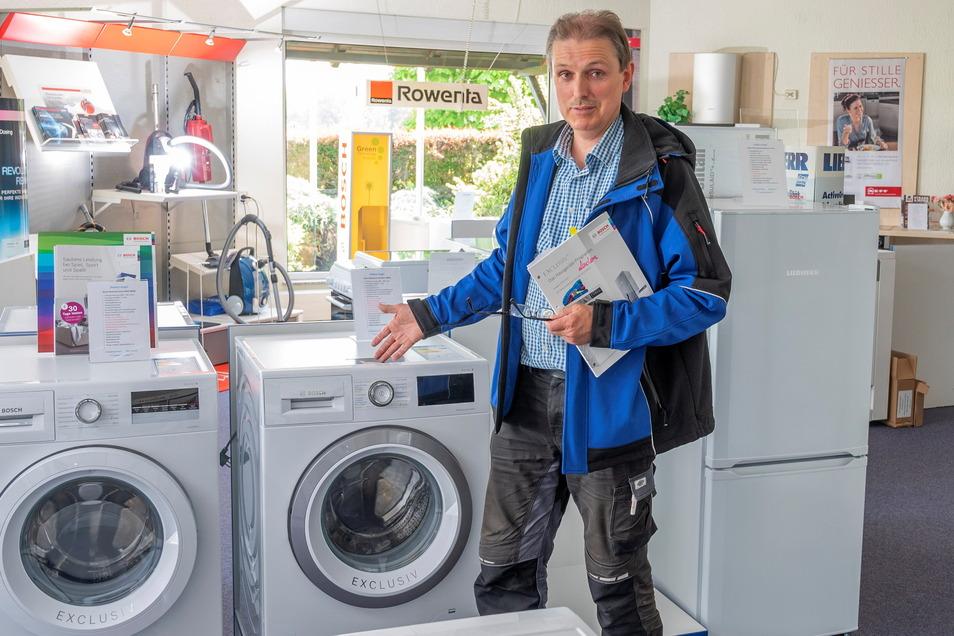 Firmenchef Jens Vogel erklärt im Verkaufsraum eine Bosch-Waschmaschine. Kunden können auch unter Corona-Bedingungen dort einkaufen - aber nur mit Termin.