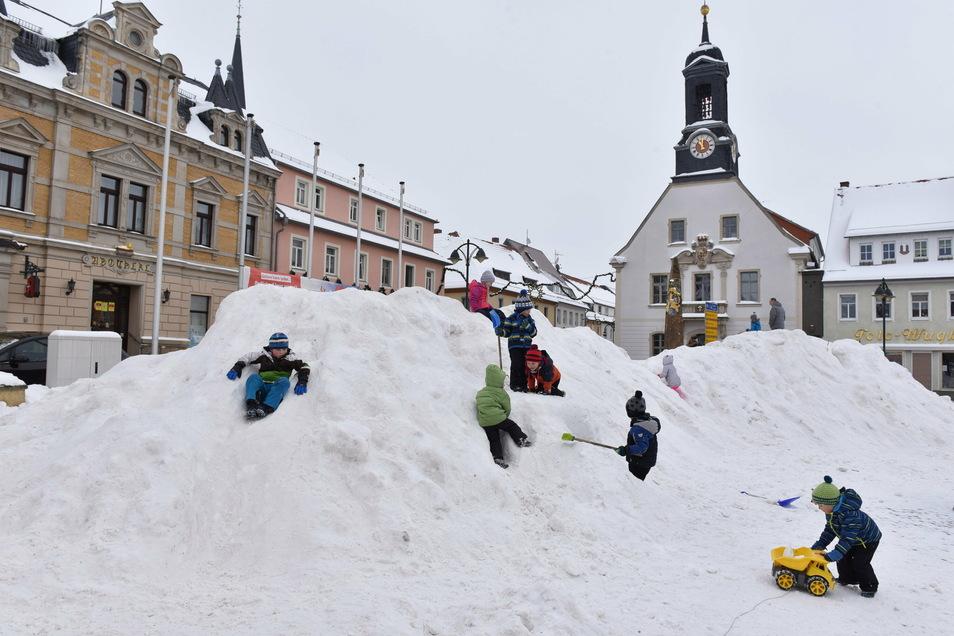 Die Kinder haben ihren Spaß mit dem aufgeschütteten Rodelberg auf dem Markt Wilsdruff.
