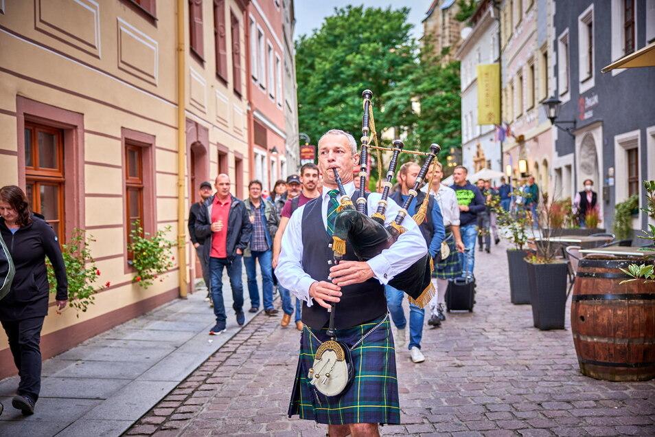 """Die Whiskyreise geht los: Ulf Hainich von den """"Dresden Bagpipes"""" lockt die Gäste aus Billys Old English Pub in Pirna zum Busparkplatz."""