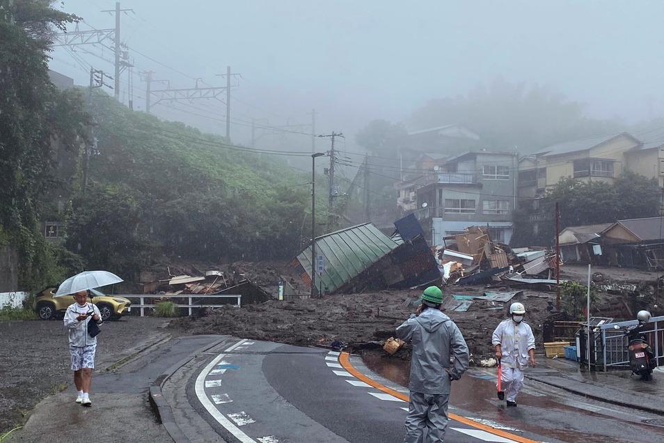 Japan, Atami: Eine Straße ist nach starkem Regen mit Schlamm, Geröll und Trümmern bedeckt.