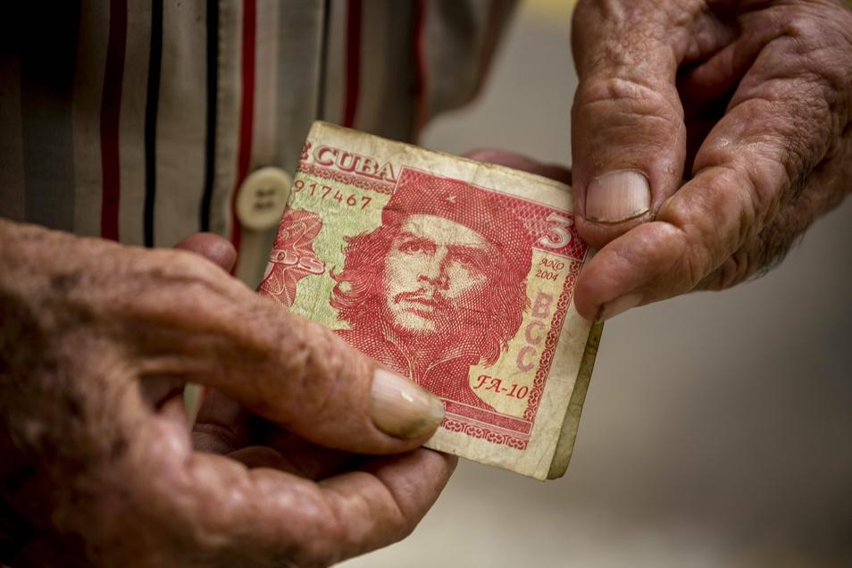 Kubaner mit einem drei Peso Geldschein mit dem Portrait von Ernesto Che Guevara.
