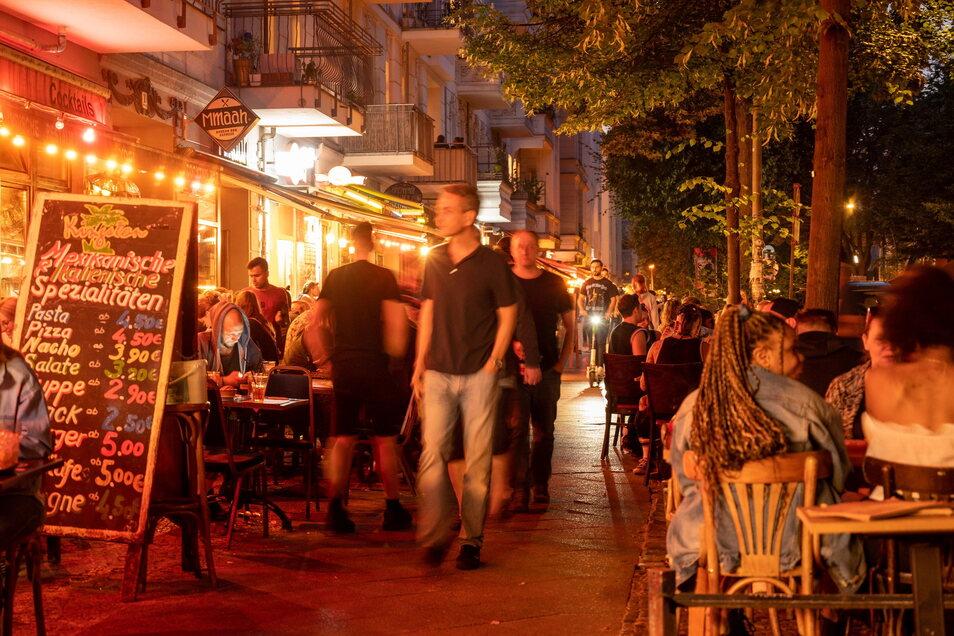 Menschen sitzen in Restaurants und Bars in Berlin-Friedrichshain: Vielerorts in Deutschland steigt die 7-Tage-Inzidenz. Dennoch werden Rufe nach Lockerungen lauter.