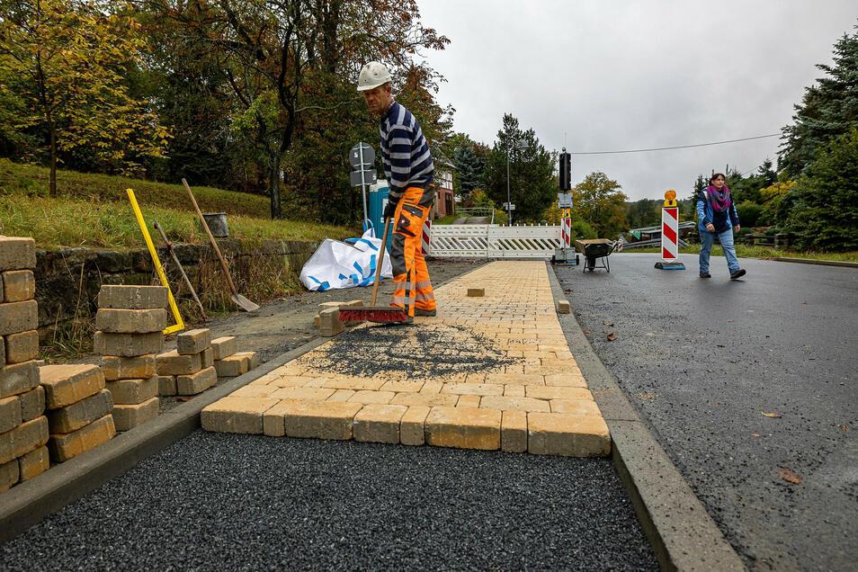 Thomas Klein pflastert den neuen Fußweg in Pfaffendorf.