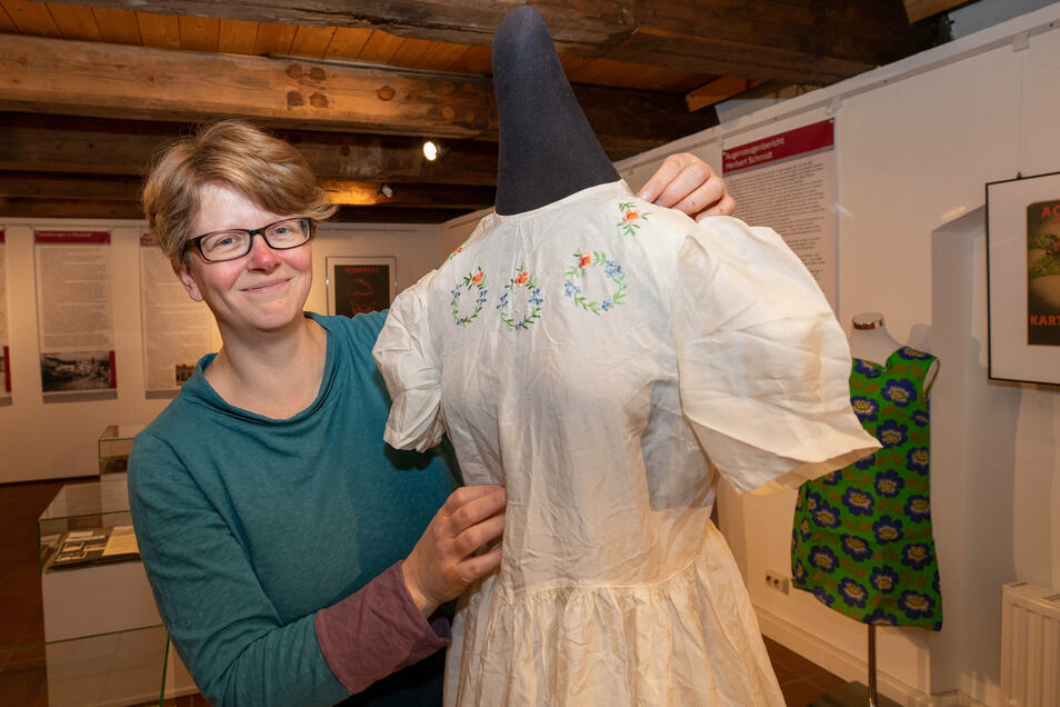 Museumsleiterin Ulrike Hentzschel zeigt ein Kleid aus Fallschirmseide.