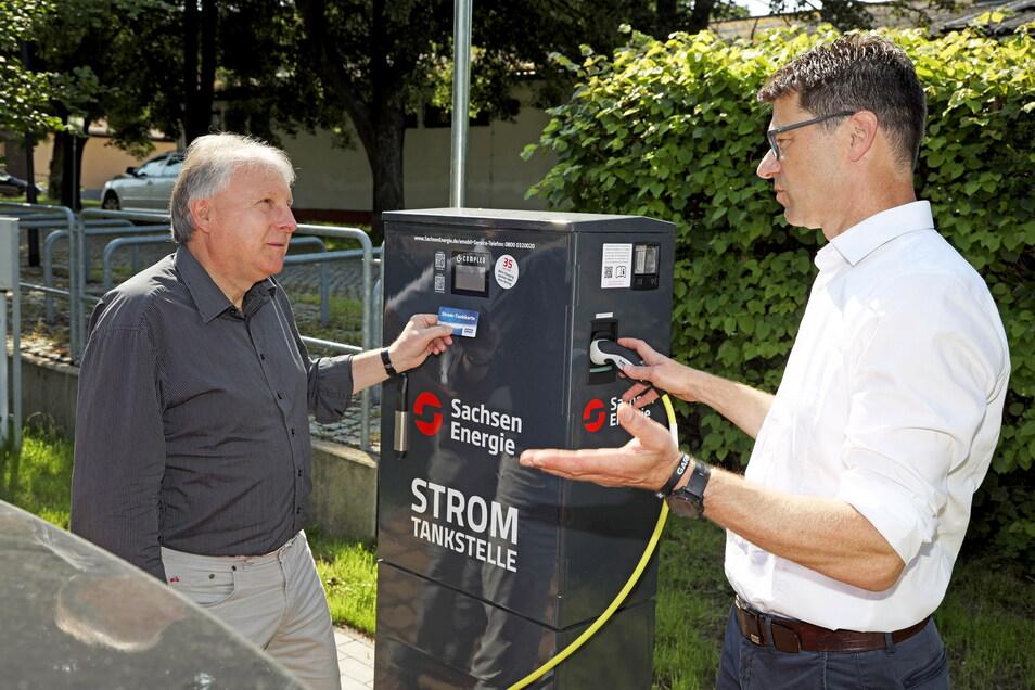Bürgermeister Gerd Barthold (links) lässt sich von Gunnar Schneider die Funktionsweise der neuen Stromtankstelle auf dem Schlossparkplatz in Diesbar-Seußlitz erklären.