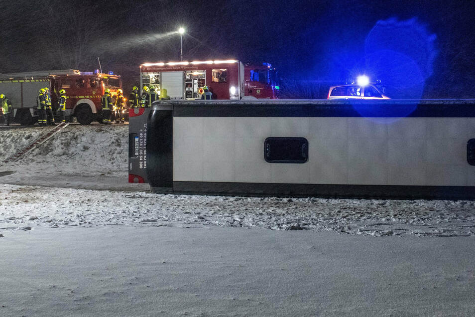 Ein Reisebus liegt umgestürzt neben der B10 in einem Feld.
