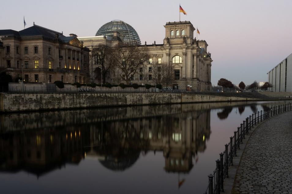 Der Reichstag spiegelt sich am frühen Morgen in der Spree. Im Bundestag wurden jetzt die Ordnungsmaßnahmen verstärkt.