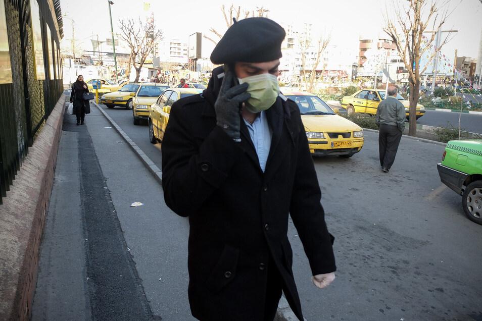 Ein Mann trägt Mundschutz und Handschuhe während er telefonierend eine Straße entlang geht.