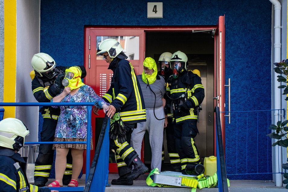 Feuerwehrleute holten die Menschen mit Masken aus dem Haus, die vor den giftigen Dämpfen schützen.