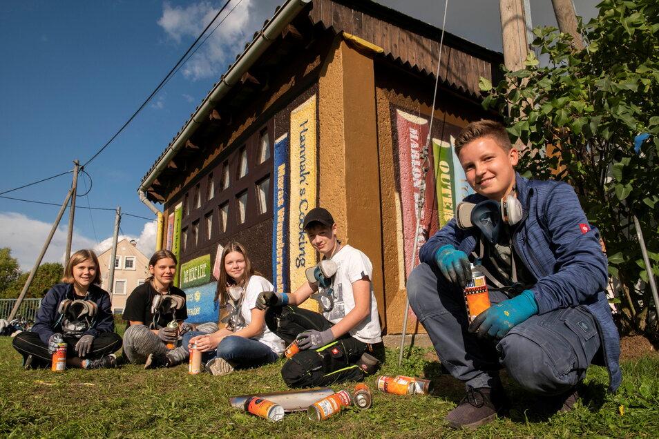 Graffiti-Bücherregal am Wartehäuschen: Schüler der Oberschule Schönfeld präsentieren ihr GTA-Projekt im Thiendorfer Ortsteil Lötzschen. Von links nach rechts : Hannah, Lexa, Hedda, Marlon und Johannes.