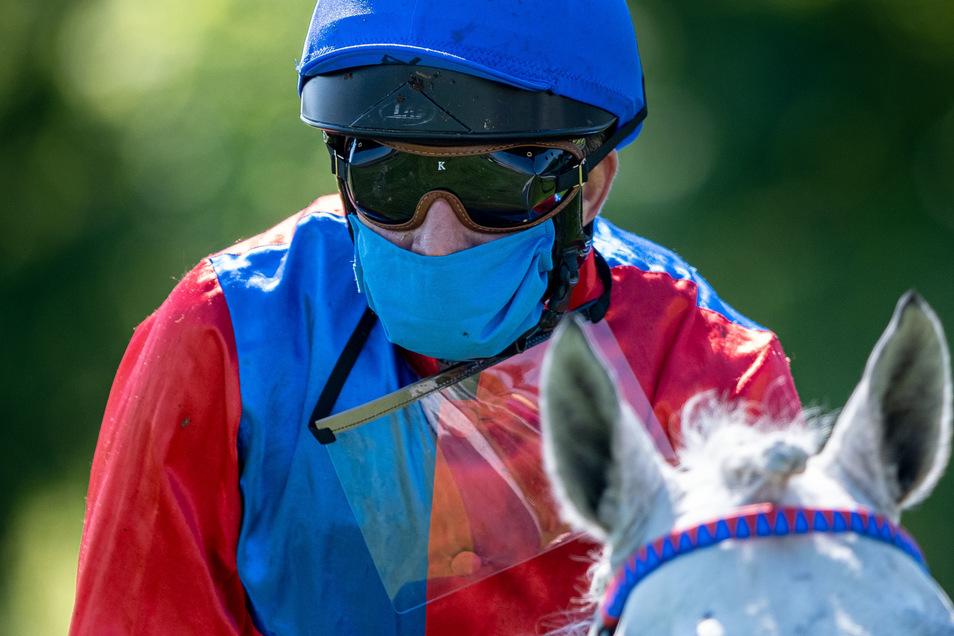 Mit Mundschutz, ohne Zuschauer: Die Jockeys reiten am Freitag in Dresden vor leeren Tribünen.