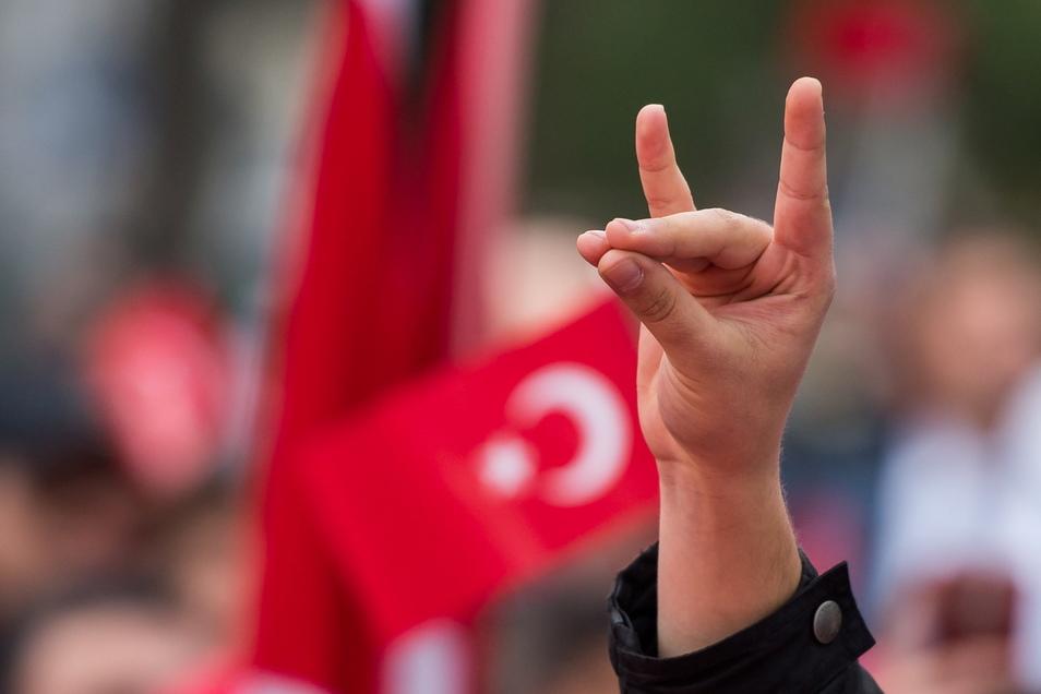"""Eine Hand zeigt den """"Wolfsgruß"""" der Grauen Wölfe während einer Demonstration."""