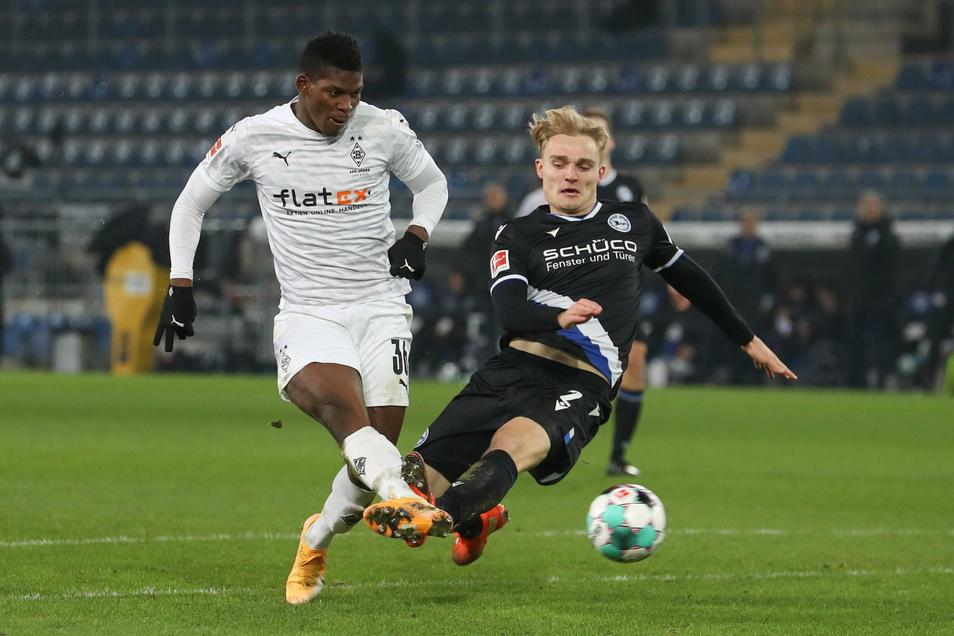 Borussia Mönchengladbachs Breel Embolo (l) erzielt den Treffer zum 0:1 gegen den Bielefelder Amos Pieper (r). Jetzt darf er wegen eines möglichen Corona-Verstoßes nicht mehr mitspielen.