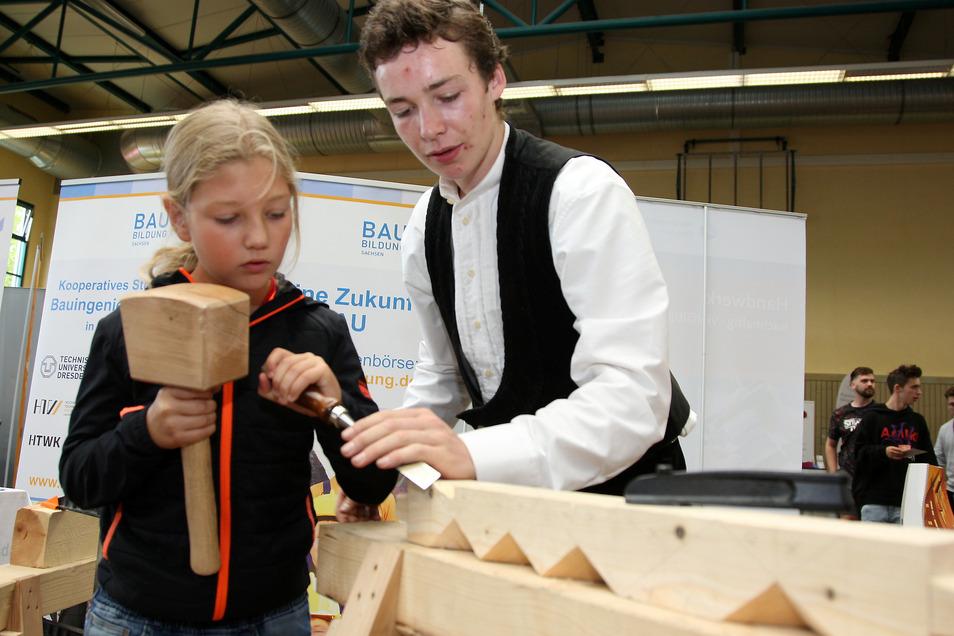 Ludwig Henke aus Naundorf ist Zimmererlehrling. Beim Tag der Ausbildung zeigt er Emilio, wie man mit einem Stemmeisen Holz bearbeitet.