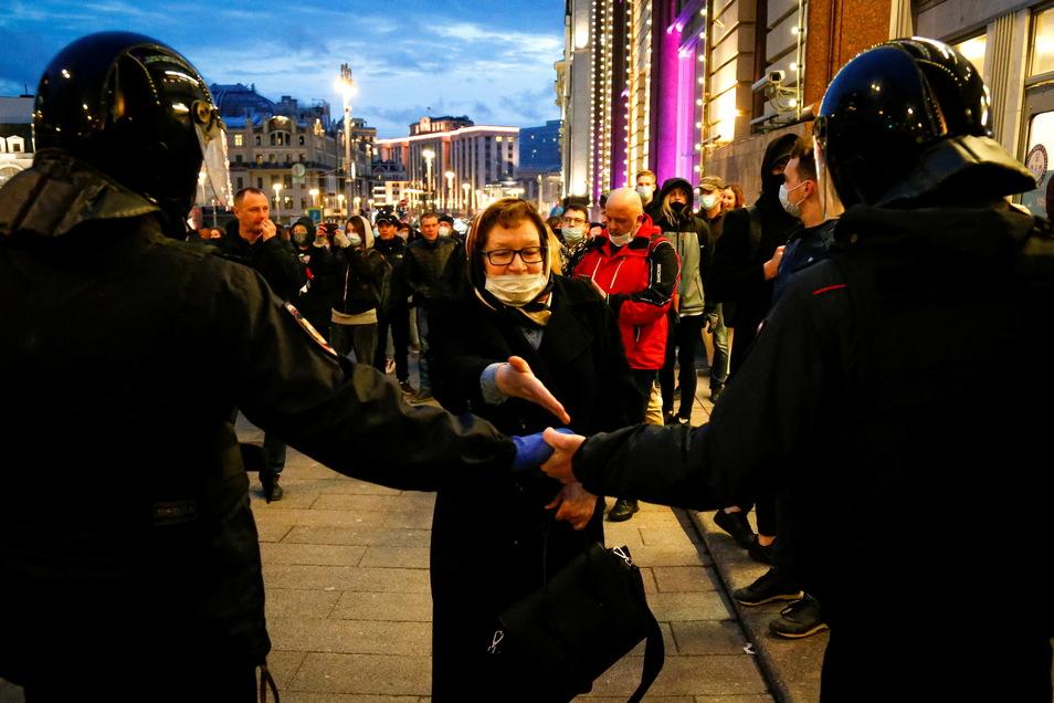 Demonstranten in Moskau vor Bereitschaftspolizisten, die eine Straße blockieren.
