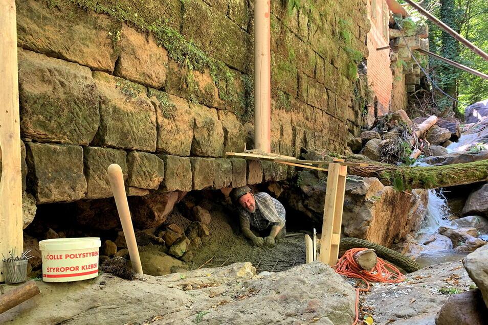 Gefährlicher Einsatz: Christoph Büttner verfüllt das Loch in der Stützmauer mit Beton und Steinen.