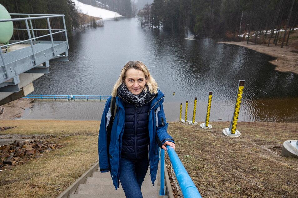 Birgit Lange von der Landestalsperrenverwaltung steht vor dem angestauten Hochwasserrückhaltebecken im Pöbeltal.