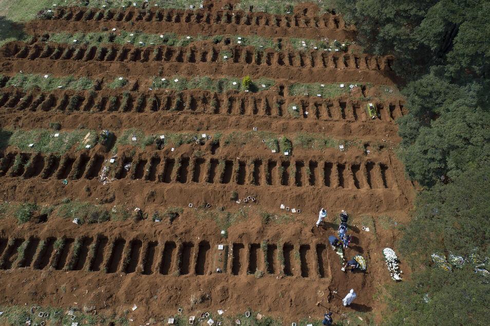 Brasilien, Sao Paulo: Mitarbeiter des Friedhofs der Vila Formosa, auf dem dutzende offene Gräber zu sehen sind, stehen neben einem geschlossenen Grab, auf das Besucher Blumen legen.