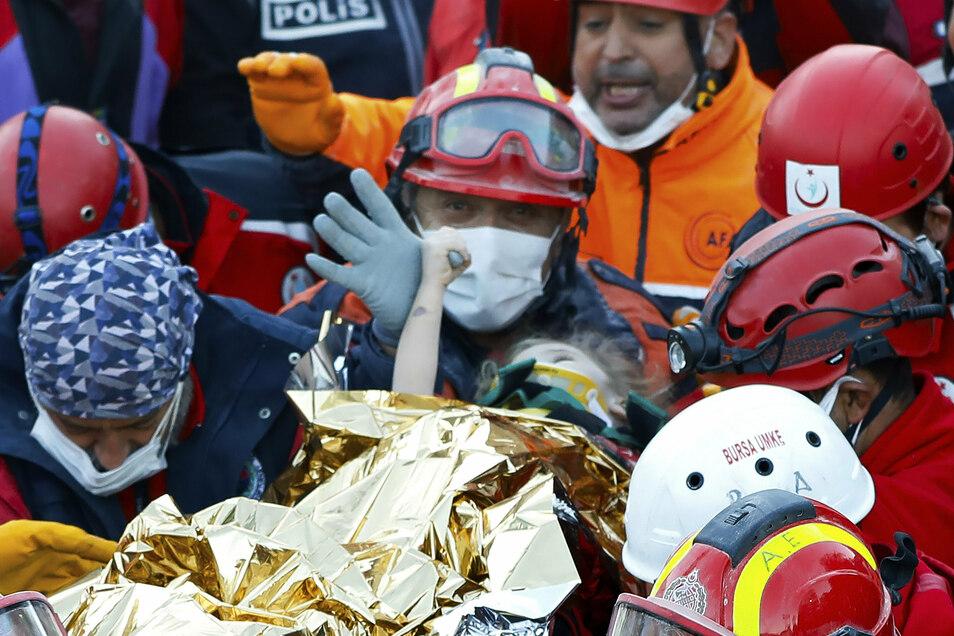 Mitarbeiter und Helfer verschiedener Rettungsdienste tragen ein dreiähriges Mädchen aus den Trümmern.