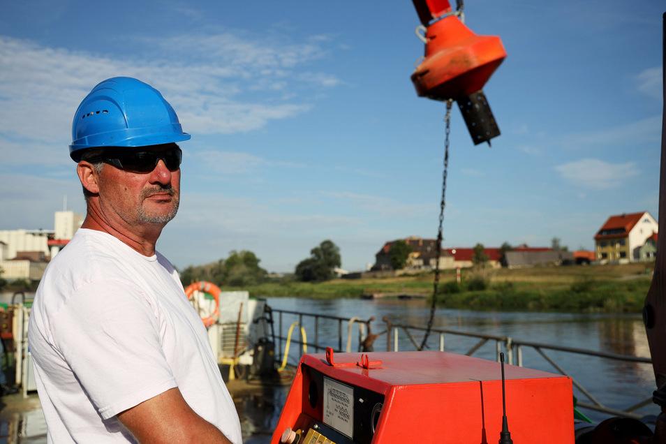 Matrose Karsten Wyrwoll vom Wasserstraßen- und Schifffahrtsamt steuert den Kran an Bord, der die Tonnen heraus und später wieder herein hebt.