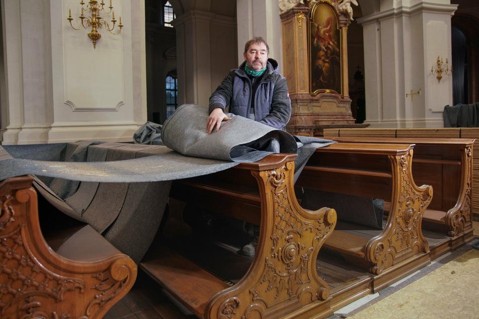 Vorarbeiter Frank Pallmer beseitigt die Filzbahnen, die während der Instandsetzung die Kirchenbänke geschützt haben.