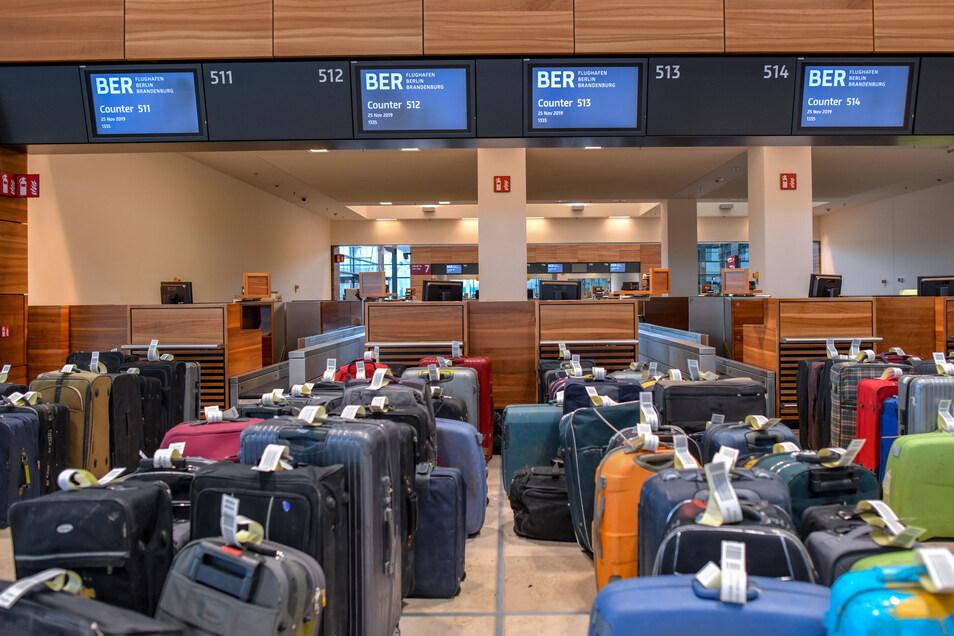 Viele Reisekoffer stehen zu Testzwecken vor Check-in-Schaltern im Terminalgebäude des Hauptstadflughafens Berlin Brandenburg Willy Brandt (BER).