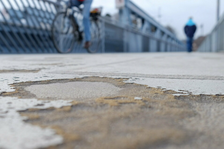 Wie eine Kraterlandschaft erscheint der Weg auf der Fußgängerbrücke über die Elbe.