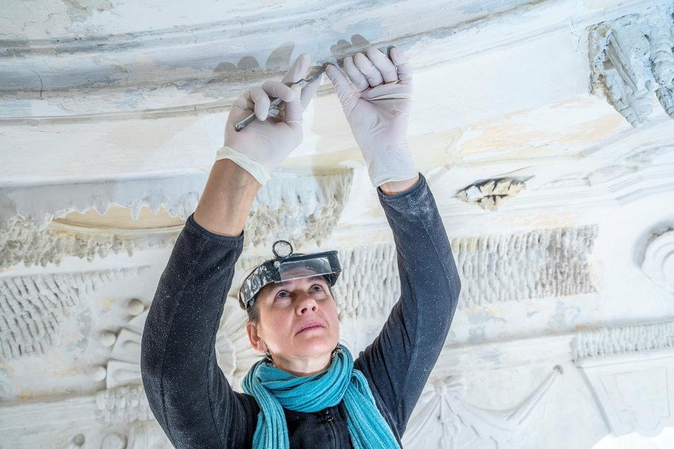 Diplom-Restauratorin Martina Dürrschmidt kratzt behutsam mit einem Spachtel die Farbe an der Decke des Pavillons ab.