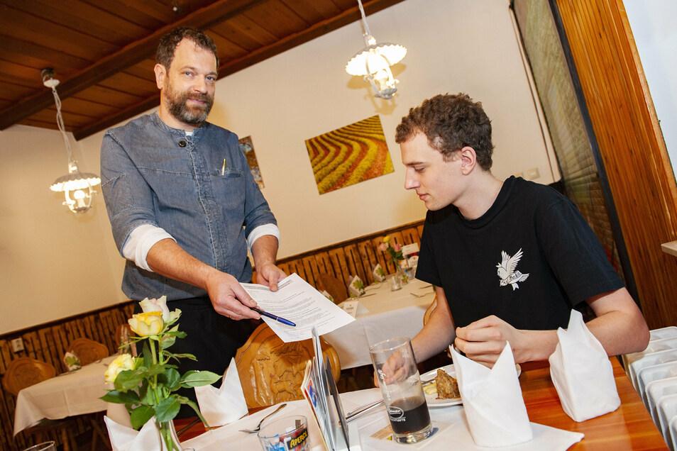 Kupferberg-Gastwirt Kai Michael Riepert bittet Leon Glöckner um seine Daten laut der neuen Corona-Schutzverordnung.