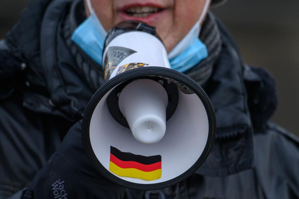 Der Organisator spricht durch ein Megafon, auf dem eine Deutschlandflagge klebt, zu den Teilnehmern.