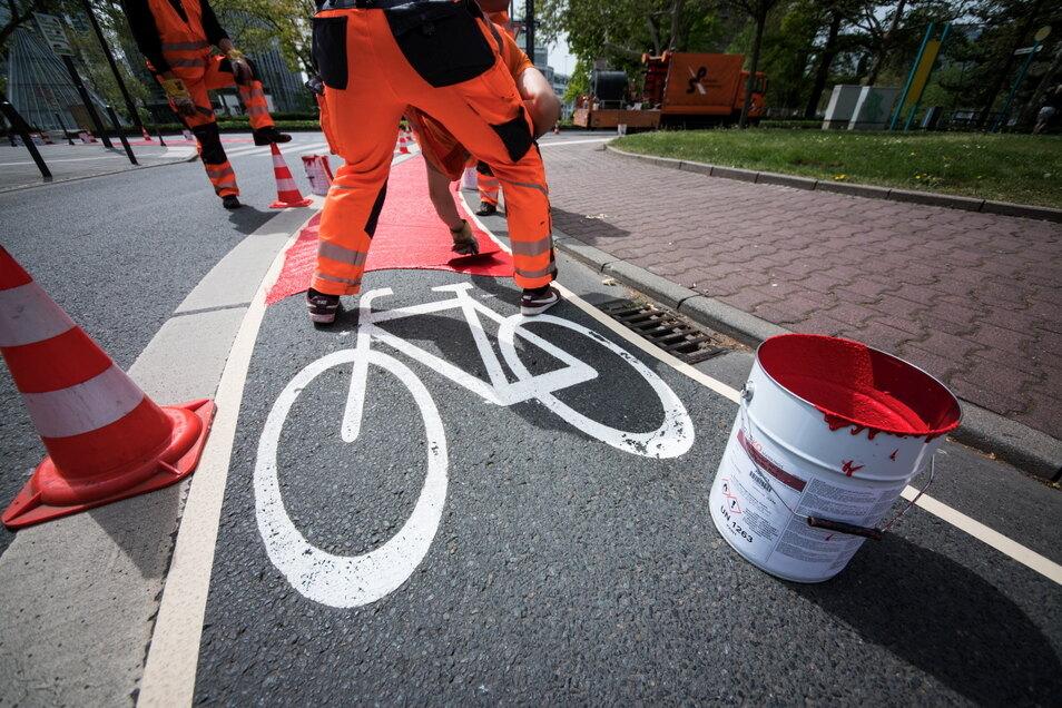 Ein Arbeiter streicht Signalfarbe auf einen Radweg. In Sachsen sind noch 450 Kilometer zu sanieren oder komplett neu zu bauen. Geht das im bisherigen Tempo weiter, braucht man dafür 28 Jahre.
