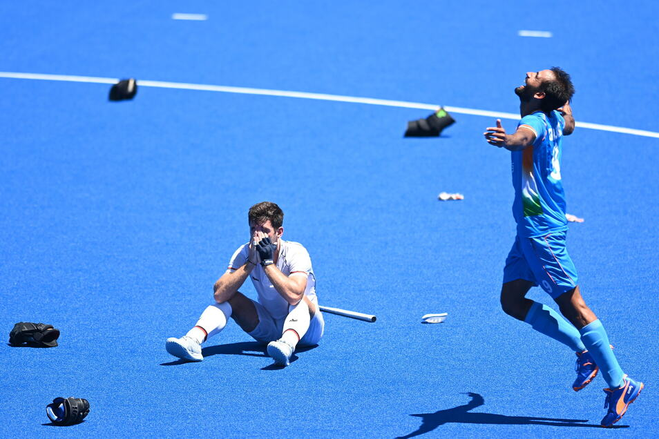 Gurjant Sing aus Indien jubelt nach dem Gewinn der Bronzemedaille. Lukas Windfeder sitzt enttäuscht daneben auf dem Boden.