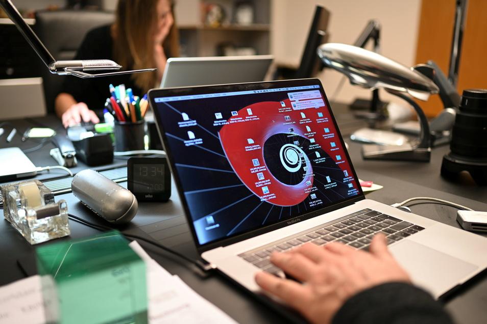 Ein Mann arbeitet im Homeoffice an einem Laptop im Homeoffice, während seine Frau ihm gegenüber sitzt. Kommt jetzt die große Rückkehr in die Büros?